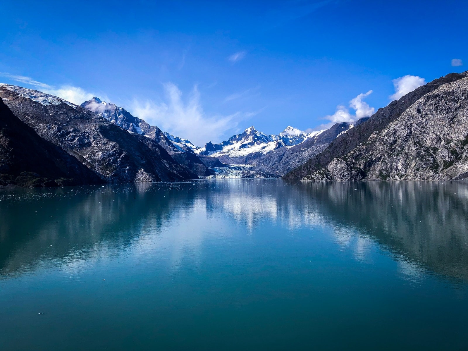 lake near snow covered mountain under blue sky during daytime
